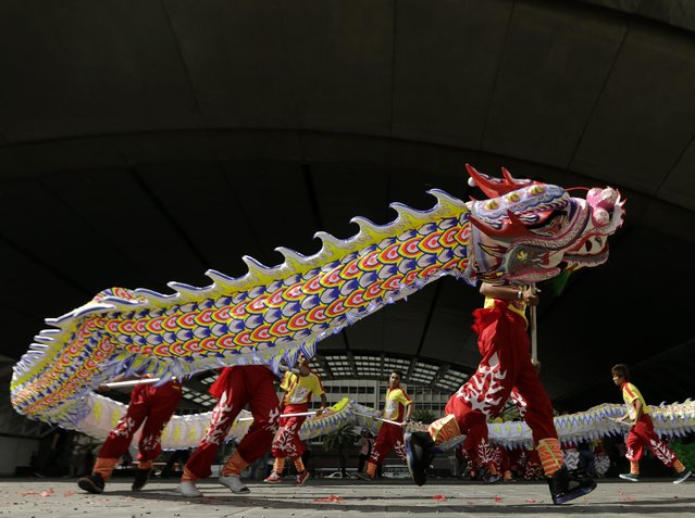Filipino dancers perform a Dragon Dance on the eve of the Chinese New Year, in front of the Philippine Stocks Exchange building in Makati city, south of Manila, Philippines, 18 February 2015. (Photo by Francis R. Malasig/EPA)