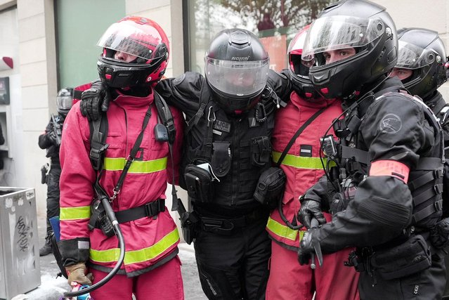 Firefighters carry police officer away from clashes during the traditional May Day protests, amid the coronavirus disease (COVID-19) outbreak in Paris, France, May 1, 2021. (Photo by Manuel Ausloos/Reuters)