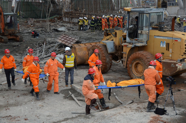 Rescue workers carry out a victim at the site where a power plant's cooling tower under construction collapsed in Fengcheng, Jiangxi province, China, November 24, 2016. (Photo by Reuters/Stringer)