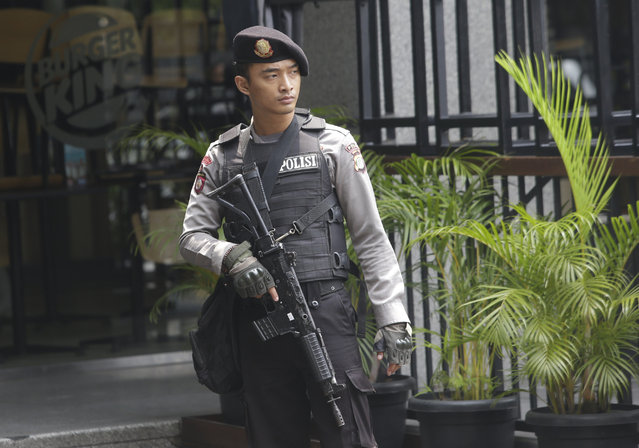 An armed policeman stands in front of a Burger King restaurant near the Starbucks cafe where Thursday's attack occurred in Jakarta, Indonesia, on Friday, January 15, 2016. (Photo by Tatan Syuflana/AP Photo)