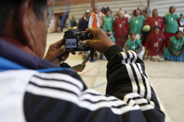 In this February 11, 2105 photo, a photographer takes a group picture of elderly Aymara indigenous women who play handball together in El Alto, Bolivia. The city's health program for seniors so far has spread to almost half of the city's districts. (Photo by Juan Karita/AP Photo)