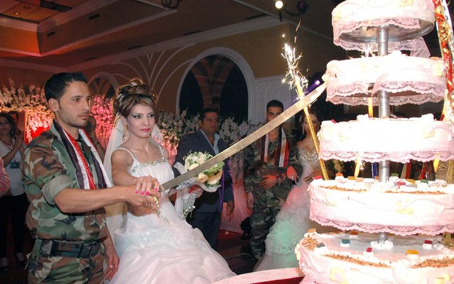 Photo released by the news agency of the Syrian government shows a soldier forces of Bashar al-Assad cutting the wedding cake with a bride during mass ceremony in which several soldiers were married in Homs, on Oktober 10, 2013. (Photo by AFP Photo/Sana)