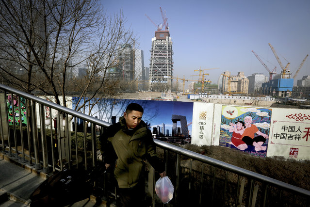 """A man carries his luggage and a bag of fruits past billboards showing Chinese government propaganda """"China Dream"""" and the scenic of Central Business District near a construction site in Beijing, Tuesday, January 19, 2016. (Photo by Andy Wong/AP Photo)"""