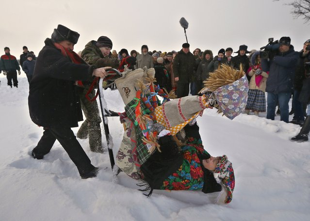 Belarusians wearing national costumes celebrate a Pull the Kolyada Up the Oak rite in the village of Martsiyanauka, some 77 km (48 miles) east of capital Minsk, Belarus, Thursday, January 21, 2016. (Photo by Sergei Grits/AP Photo)