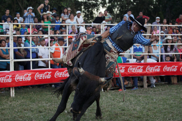 A rodeo bullfighter goes flying off the bull during the bull riding event in Santa Tecla, El Salvador, December 15, 2016. (Photo by Jose Cabezas/Reuters)