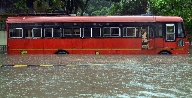 A driver looks out from inside a bus stucked in a waterlogged raod during a heavy monsoon rainfall in Mumbai on June 9, 2021. (Photo by Sujit Jaiswal/AFP Photo)