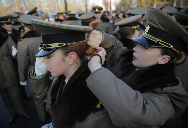 A military cadet gets help from a colleague to adjust her hair before taking part the military parade in Bucharest, Romania, Saturday, December 1, 2018. (Photo by Vadim Ghirda/AP Photo)