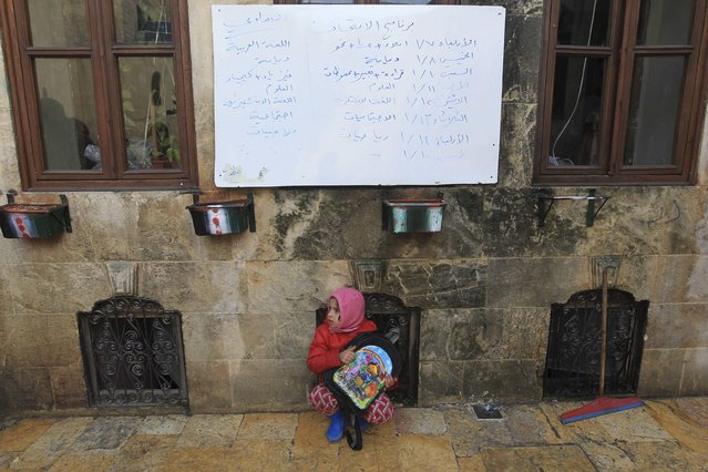 A girl sits under a whiteboard inside a school in Old Aleppo January 3, 2015. (Photo by Jalal Al-Mamo/Reuters)