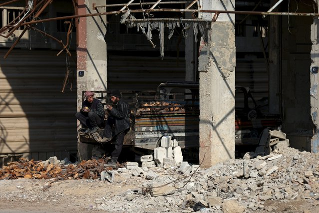 Firewood vendors eat on the back of a pickup truck in Douma, Syria February 3, 2016. (Photo by Bassam Khabieh/Reuters)