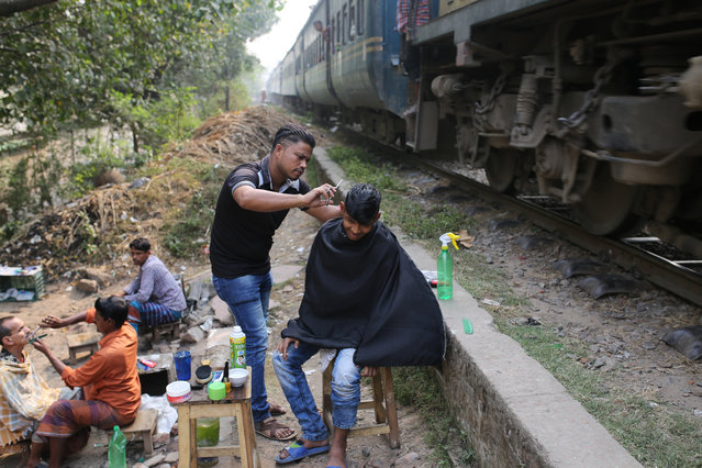Street barbers at work next to a railway near the city Dhaka, Bangladesh on November 21, 2018. (Photo by Rehman Asad/Barcroft Images)