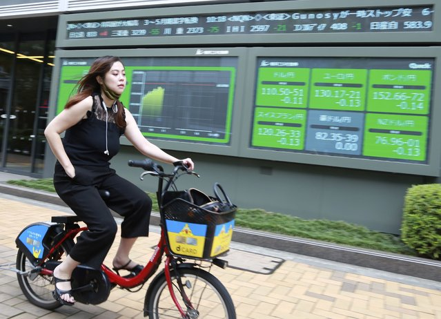 A woman cycles past an electronic stock board of a securities firm in Tokyo, Wednesday, July 14, 2021. (Photo by Koji Sasahara/AP Photo)