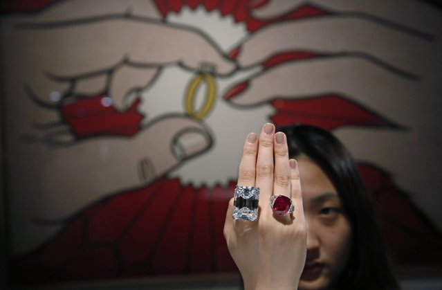 A model displays a 100.20-carat diamond, left, and a 25.59-carat Burmese ruby during a media preview for the Sotheby's auction in Hong Kong Friday, April 3, 2015. The diamond, a 100.20-carat perfect D color, internally flawless, Type IIa stone in a classic emerald-cut, will be offered in New York Sotheby's auction house on April 21, when it is estimated to sell for US$19-25 million. (Photo by Kin Cheung/AP Photo)