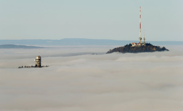 Fog covers the landscape around the peak of Uetliberg mountain (869m/2,850 feet above sea level) and the Felsenegg broadcast tower (L) in Zurich, Switzerland December 21, 2016. (Photo by Arnd Wiegmann/Reuters)