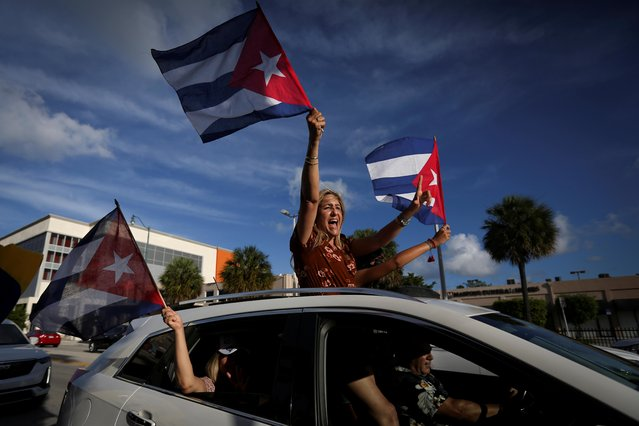A woman shouts and waves a Cuban flag as drives past outside Versailles restaurant, in reaction to reports of protests in Cuba against its deteriorating economy, in Miami, Florida, U.S. July 18, 2021. (Photo by Marco Bello/Reuters)