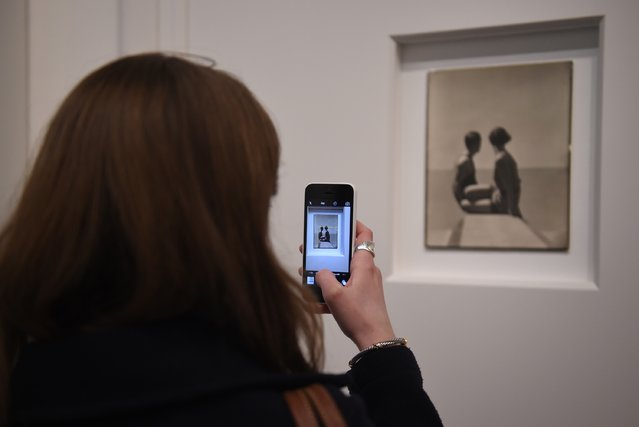 "A journalist uses their phone to take a picture at the press preview for ""Vogue 100: A Century of Style"" exhibiting the photographs that has been commissioned by British Vogue since it was founded in 1916 at National Portrait Gallery on February 10, 2016 in London, England. (Photo by Stuart C. Wilson/Getty Images)"