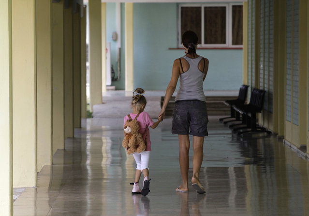 A Ukrainian girl, Olga, 2, victim of the 1986 nuclear power plant disaster in Chernobyl, walks with a Cuban physiotherapist at the Pediatric Hospital in Tarara, outside Havana, March 2010. (Photo by Desmond Boylan/Reuters)