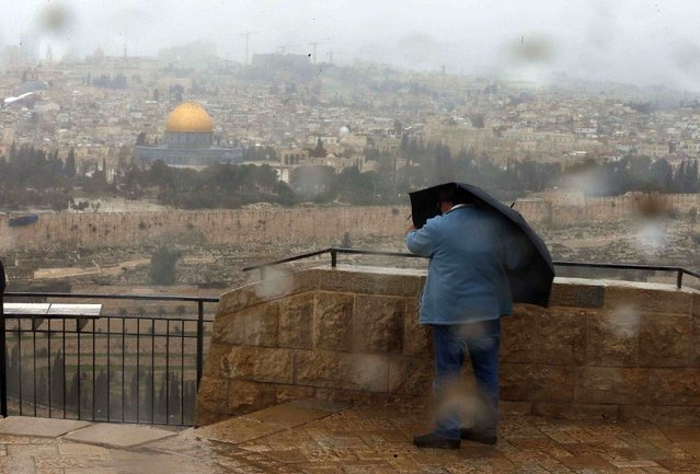 The Dome of the Rock is seen in the background as a tourist holds her umbrella during a gust of wind outside Jerusalem's Old City February 19, 2015. (Photo by Ammar Awad/Reuters)