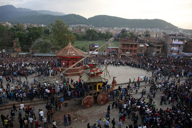 """Nepalese devotees take down the """"lingo"""" a long wooden pole symbolizing a phallus, erected a day earlier with the belief that it will bring happiness and good harvest, during the Bisket festival at Bhaktapur, Tuesday, April 14, 2015. (Photo by Niranjan Shrestha/AP Photo)"""