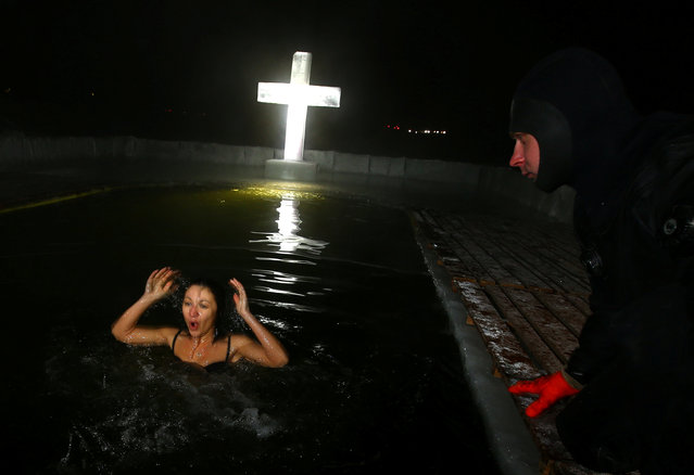 A woman takes a dip in the icy waters of a lake during Orthodox Epiphany celebrations in Minsk, Belarus, January 18, 2017. (Photo by Vasily Fedosenko/Reuters)