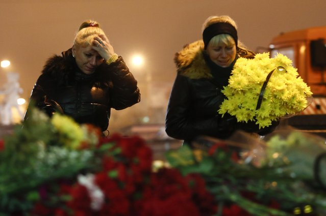 Women cry laying flowers outside the Volgograd main railway station in Volgograd, Russia, early Monday December 30, 2013. (Photo by Denis Tyrin/AP Photo)
