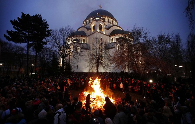 People burn dried oak branches, which symbolize the Yule log, on Orthodox Christmas Eve in front of the St. Sava temple in Belgrade, on January 6, 2014. Serbian Orthodox Christians celebrate Christmas on January 7, according to the Julian calendar. (Photo by Marko Djurica/Reuters)