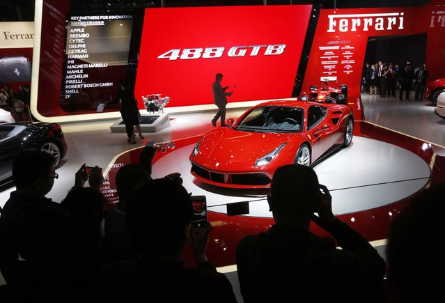 Visitors take photos of the Ferrari 488 GTB on display at the Ferrari booth at the 16th Shanghai International Automobile Industry Exhibition in Shanghai, China, 20 April 2015. (Photo by How Hwee Young/EPA)
