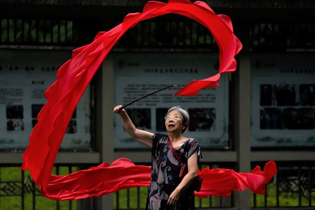 A woman twirls a banner for exercise at a public park in Beijing, Thursday, September 9, 2021. (Photo by Mark Schiefelbein/AP Photo)
