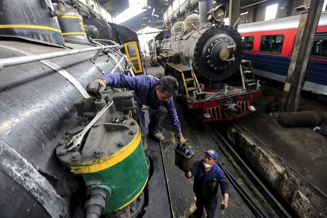 "Mechanics work on a ""La Sabana"" tourist train steam locomotive manufactured in 1934 at their workshop in Bogota, March 2, 2015. (Photo by Jose Miguel Gomez/Reuters)"