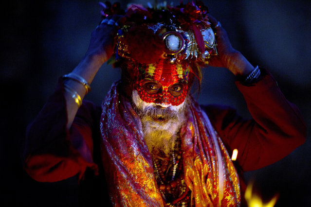 A Hindu holy man with his face smears with ash and vermilion powder adjusts his head gear sitting at the courtyard of the Pashupatinath Temple during Shivaratri festival in Kathmandu, Nepal, Monday, March 4, 2019. Shivaratri, or the night of Shiva, is dedicated to the worship of Lord Shiva, the Hindu god of death and destruction. (Photo by Niranjan Shrestha/AP Photo)