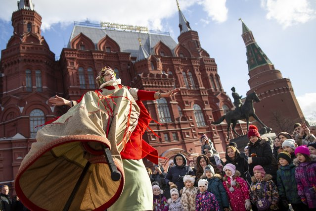 An artist performs during Maslenitsa (Shrovetide) holiday celebrations in front of the Historical Museum in Manezhnaya Square near the Kremlin Wall in Moscow, Russia, Saturday, March 9, 2019. Maslenitsa is a traditional Russian holiday marking the end of winter that dates back to the pagan times. (Photo by Alexander Zemlianichenko/AP Photo)