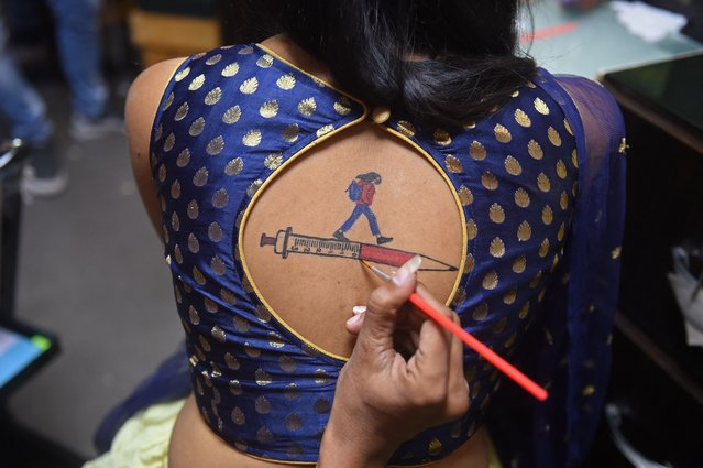 A Garba (folk dance) participant gets her back painted with an awareness message on vaccination against the Covid-19 coronavirus during the ongoing Navratri festival in Ahmedabad on October 8, 2021. (Photo by Sam Panthaky/AFP Photo)