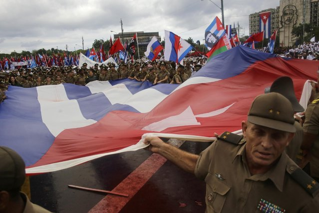 Cuban Army soldiers hold a giant Cuban flag as they march in Revolution Square marking May Day, in Havana, Cuba, Friday, May 1, 2015. (Photo by Ramon Espinosa/AP Photo)