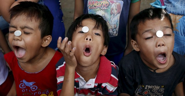 Boys take part in a coin game contest during a celebration of religious patron Nuestro Senor Jesucristo in Quezon city, Philippines May 3, 2015. The winner of the contest is the one who gets the coin inside the mouth first without touching the coin. (Photo by Erik De Castro/Reuters)