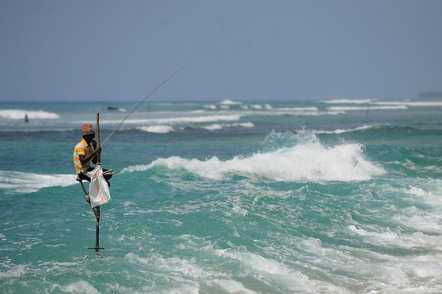 A Sri Lankan stilt fishermen works on his pole in the southern town of Galle on February 12, 2014. The number of foreign tourists visiting Sri Lanka has swelled since the island ended a 37-year separatist conflict with Tamil Tiger rebels in May 2009. (Photo by Ishara S. Kodikara/AFP Photo)
