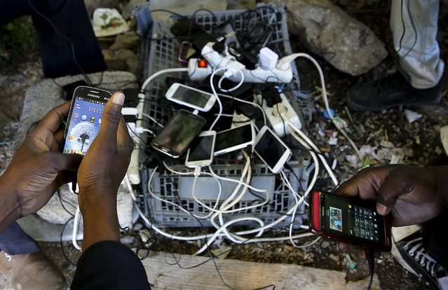 Sudanese immigrants charge their mobile phones at a make-shift electric outlet in the western Greek town of Patras May 4, 2015. (Photo by Yannis Behrakis/Reuters)