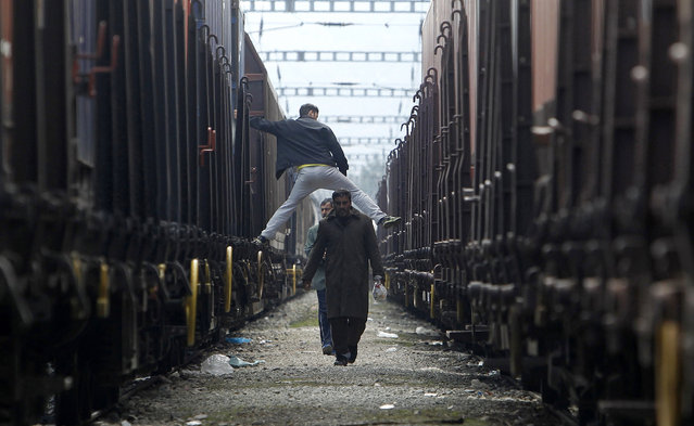 Migrants walk between trains while another, top, tries to jump from one train to another at the northern Greek border post of Idomeni, turned into a makeshift migrant camp, Friday, March 18, 2016. European Union leaders have agreed upon a common stance on a plan to send tens of thousands of migrants back to Turkey, something they proposed to Turkish Prime Minister Ahmet Davutoglu Friday. (Photo by Boris Grdanoski/AP Photo)
