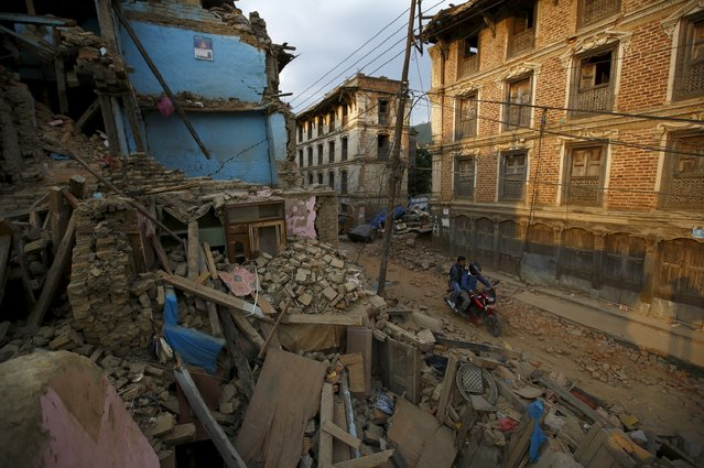 People ride a motorcycle along collapsed houses after the April 25 earthquake at Sankhu, on the outskirts of Kathmandu May 6, 2015. (Photo by Navesh Chitrakar/Reuters)