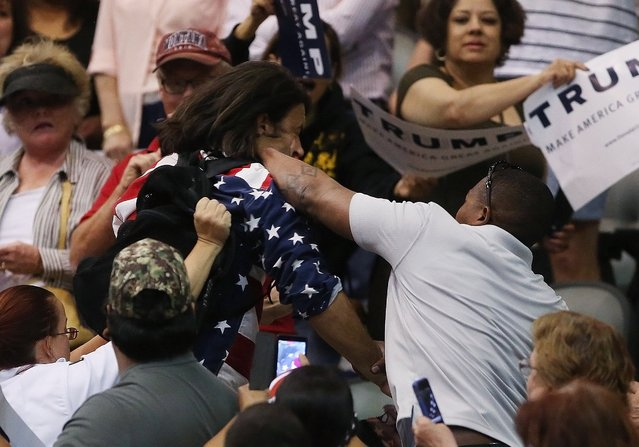 Trump protester Bryan Sanders, center left, is punched by a Trump supporter as he is escorted out of Republican presidential candidate Donald Trump's rally at the Tucson Arena in downtown Tucson, Ariz., Saturday, March 19, 2016. (Photo by Mike Christy/Arizona Daily Star via AP Photo)