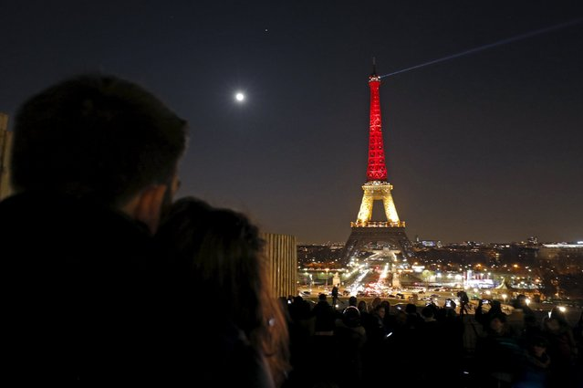 A couple looks at the Eiffel Tower lit up in the colours of the Belgian flag in tribute to the victims of today's bomb attacks in Brussels, in Paris, France, March 22, 2016. (Photo by Philippe Wojazer/Reuters)