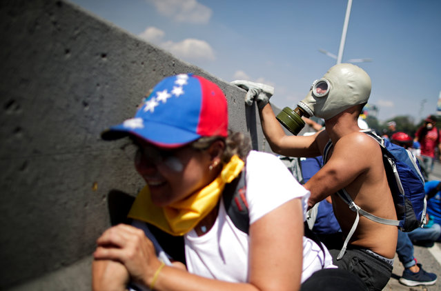 """An opposition demonstrator peers out from behind a concrete divider as others take over on a street near the Generalisimo Francisco de Miranda Airbase """"La Carlota"""", in Caracas, Venezuela April 30, 2019. (Photo by Ueslei Marcelino/Reuters)"""