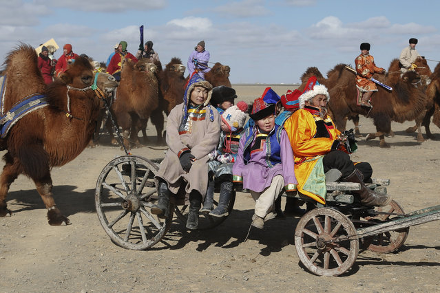 "People sit on a cart with a camel tied to it during ""Temeenii bayar"", the Camel Festival, in Dalanzadgad, Umnugobi aimag, Mongolia, March 6, 2016. (Photo by B. Rentsendorj/Reuters)"
