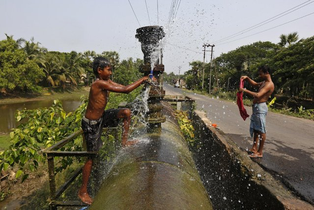 People wash in water from a broken water pipeline on the outskirts of Kolkata, India, March 30, 2016. (Photo by Rupak De Chowdhuri/Reuters)