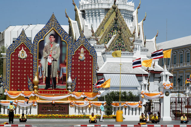 People stand in front of a portrait of Thailand's King Maha Vajiralongkorn during a rehearsal of his coronation procession which will take place next week in Bangkok, Thailand on April 28, 2019. (Photo by Jorge Silva/Reuters)