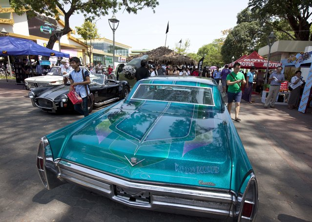 Visitors walk past 1964 model Cadillac DeVille displayed at the first Myanmar Classic Car Show organized by Myanmar Classic Car Club at Myanmar Culture Valley Saturday, May 9, 2015, in Yangon, Myanmar. (Photo by Khin Maung Win/AP Photo)