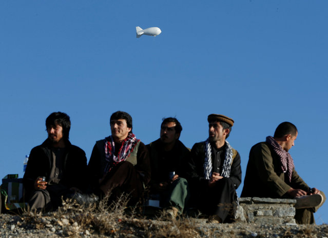 A NATO security ballon is seen in the sky as Afghan men rest on a hilltop in Kabul, Afghanistan February 23, 2017. (Photo by Omar Sobhani/Reuters)
