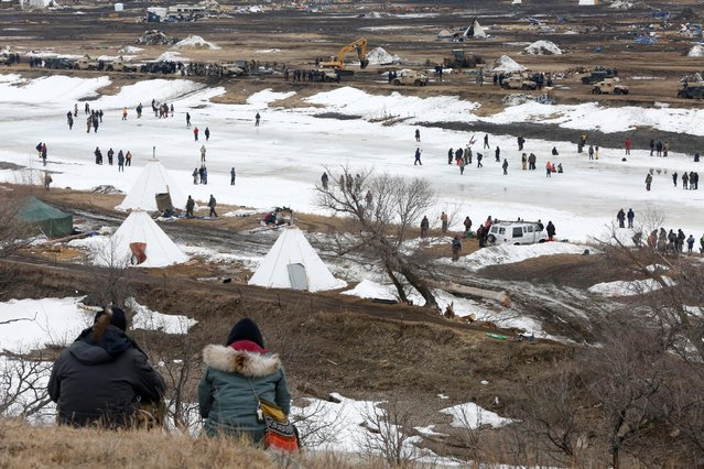Protesters watch law enforcement officers guard the edge of the main opposition camp against the Dakota Access oil pipeline near Cannon Ball, North Dakota, U.S., February 23, 2017. (Photo by Terray Sylvester/Reuters)