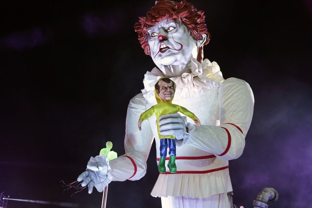 A giant statue of US President Donald Trump depicted as an evil clown holding a French President Emmanuel Macron's puppet in his hand parade during the 135th Nice Carnival on February 16, 2019 in Nice, France  (Photo by Patrick Aventurier/Getty Images)