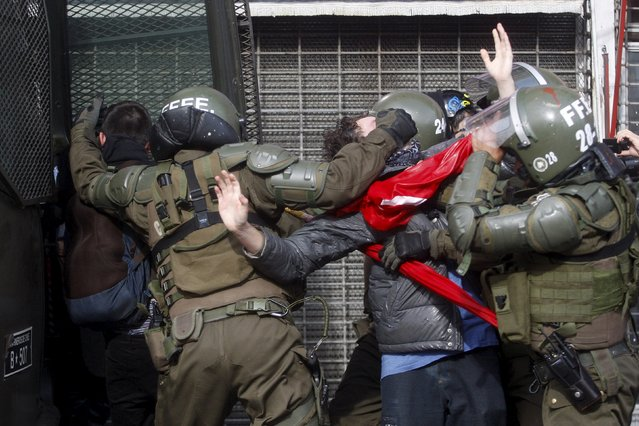 A demonstrator is detained by riot policemen during a rally, as Chile's President Michelle Bachelet delivers a speech inside the National Congress, in Valparaiso city, May 21, 2015. (Photo by Carlos Vera/Reuters)