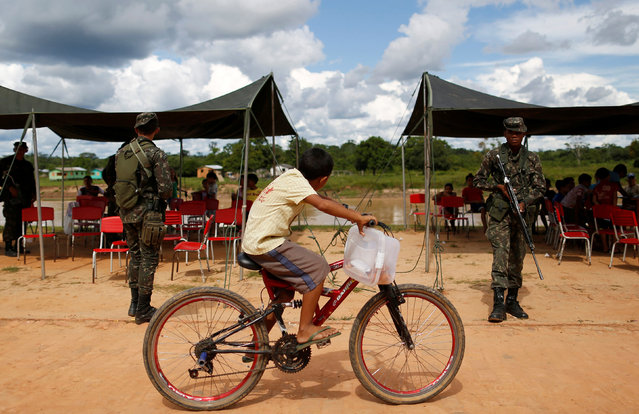 A boy rides his bicycle near Brazilian army soldiers in front of the Jurua river as the armies of Brazil, Peru and Colombia participate in an an operation to combat illegal logging and drug trafficking in the region of the triple border, according to Brazilian army, in Porto Walter, Acre state, Brazil, April 7, 2016. (Photo by Bruno Kelly/Reuters)