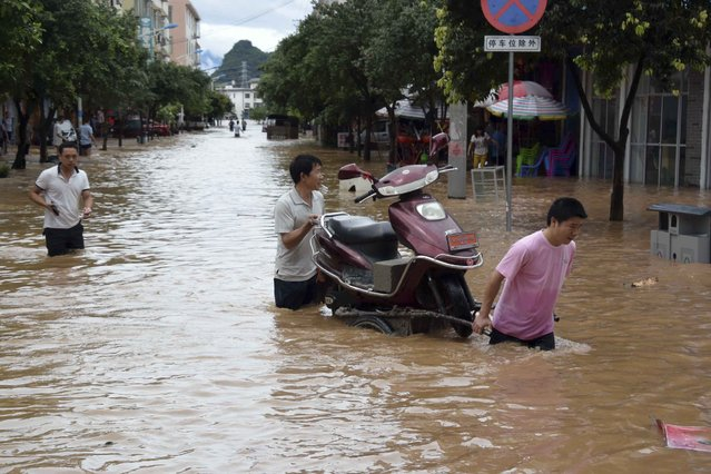 In this Thursday, May 21, 2015 photo released by China's Xinhua News Agency, residents move a motorcycle on a flooded street in Jiahui town of Gongcheng Yao Autonomous County, southwest China's Guangxi Zhuang Autonomous Region. (Photo by Zhou Hua/Xinhua via AP Photo)